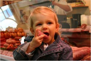 Kind vor der Fleischerei Schraps Wurst- und Fleischtheke.